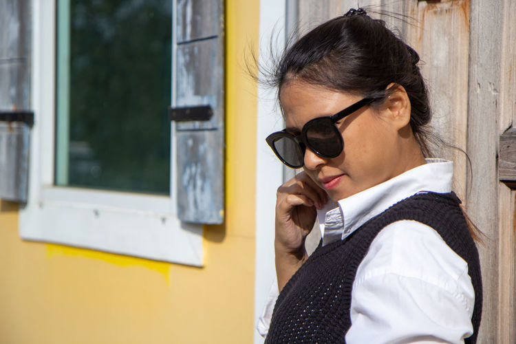 Portrait of young woman holding sunglasses at window