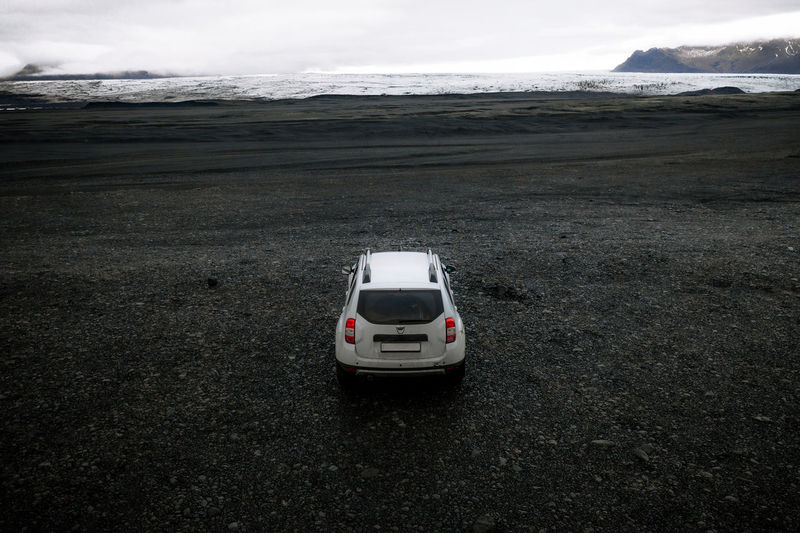 Car on land by sea against sky