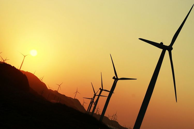 Low angle view of silhouette wind turbines against sky during sunset