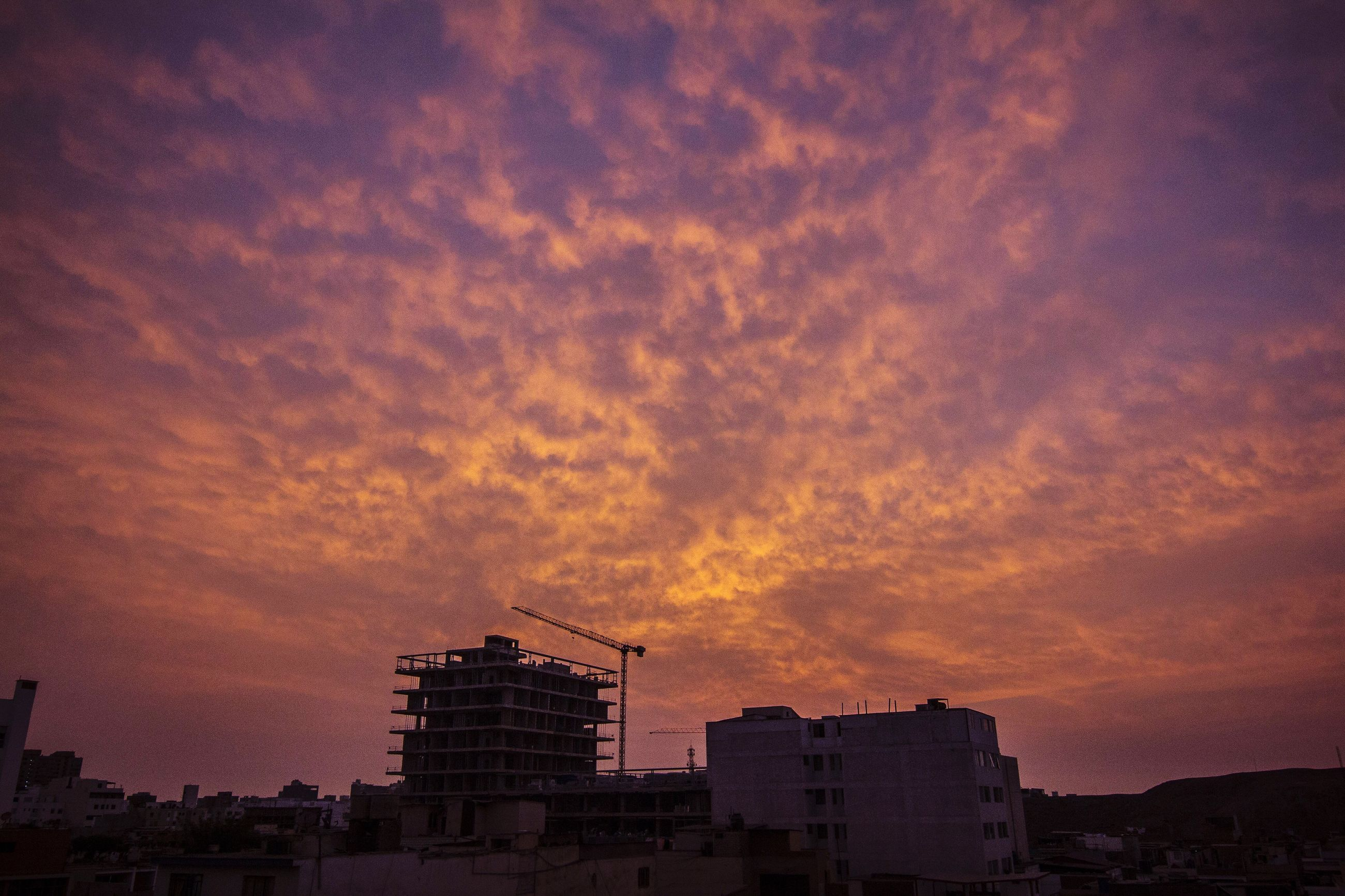 sunset, building exterior, architecture, built structure, sky, silhouette, cloud - sky, orange color, low angle view, cloudy, dramatic sky, building, weather, overcast, dusk, cloud, city, outdoors, nature, residential structure