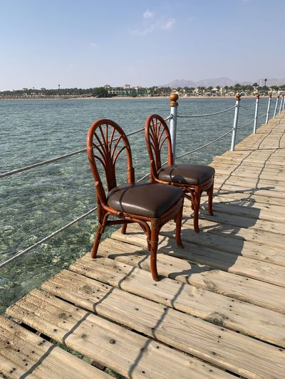 Empty chairs and table on pier by sea against sky