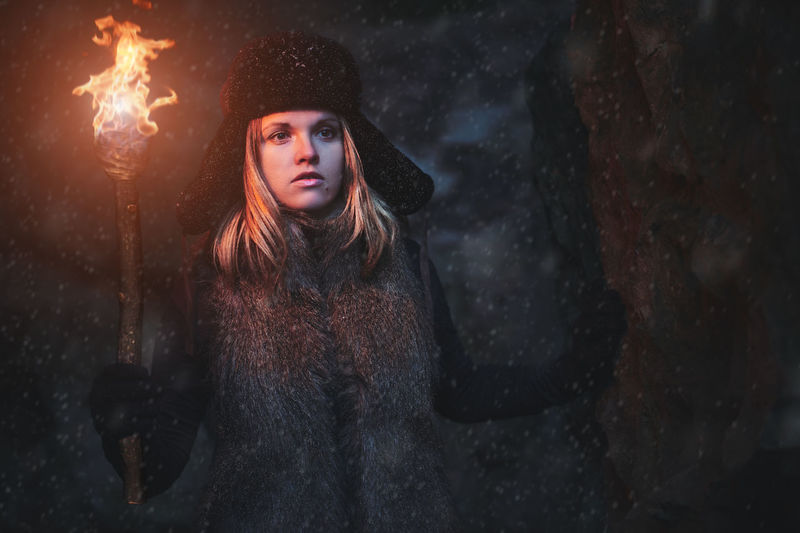 Woman with flaming torch in cave at night during winter