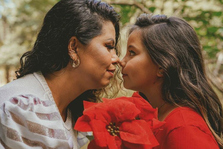 Close-up of mother and daughter holding flower embracing at park