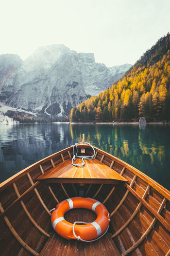 Wooden boat moored in lake by mountains