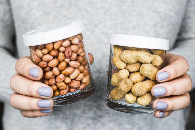 Close-up of hand holding peanut jars