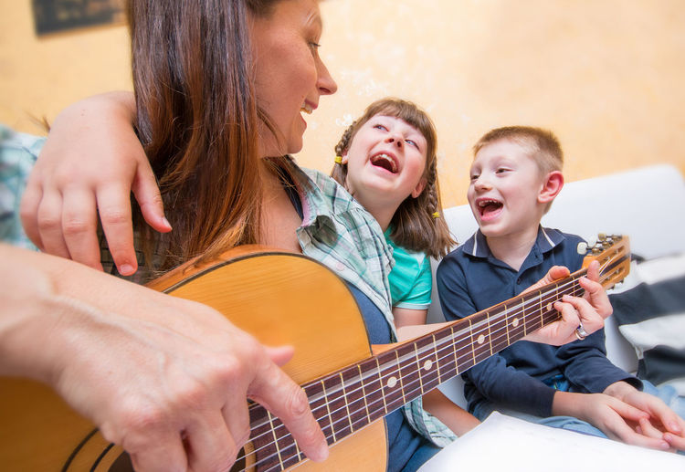 Mother playing guitar while sitting with kids at home