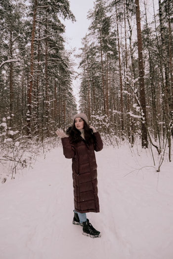 Full length of woman standing on snow covered land