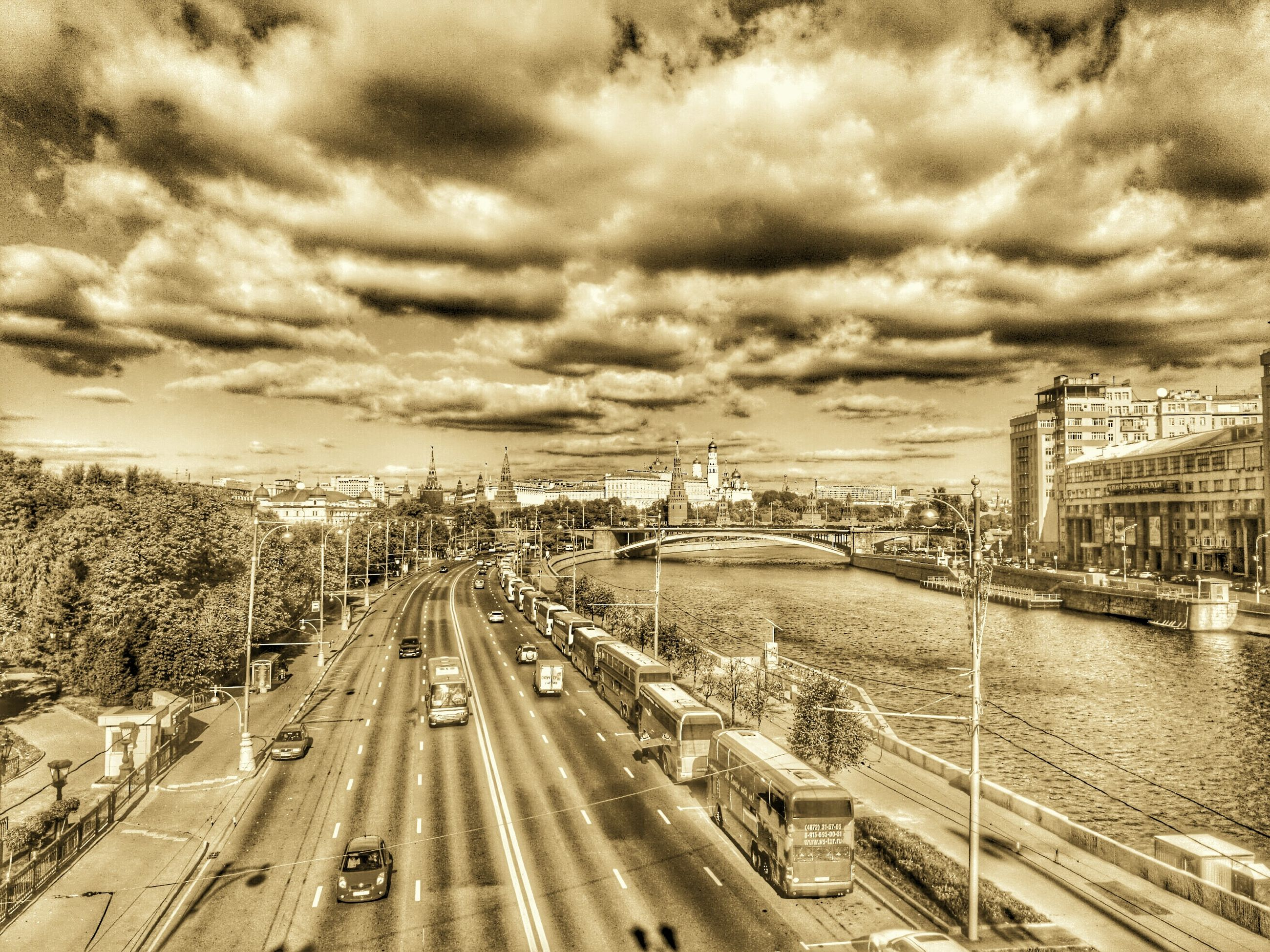 cloud - sky, sky, cloudy, architecture, building exterior, built structure, transportation, city, weather, high angle view, overcast, road, the way forward, water, car, street, cityscape, cloud, diminishing perspective, storm cloud