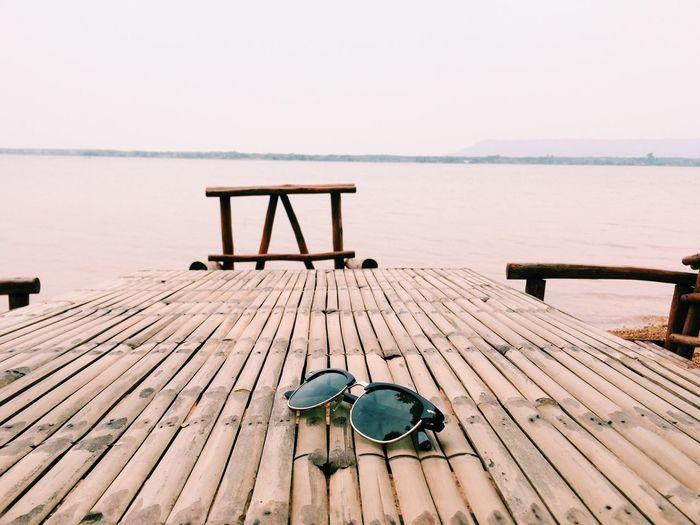 Sunglasses on pier over sea against sky