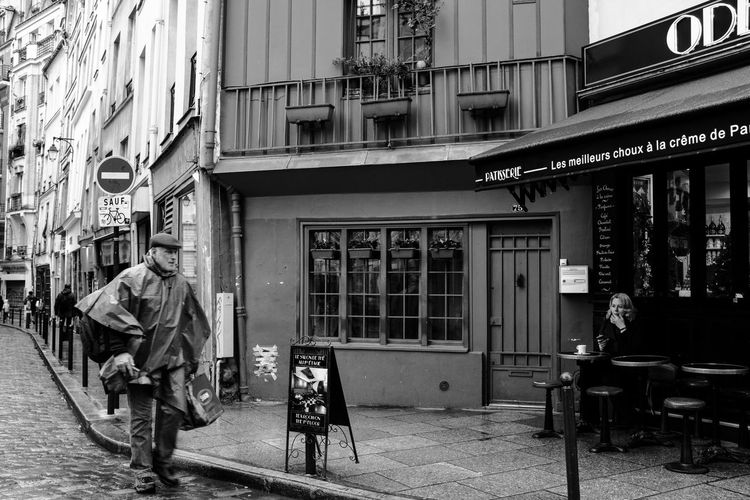People walking on sidewalk by building in city