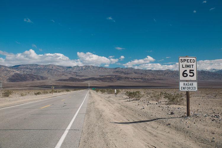 Road sign on landscape against sky