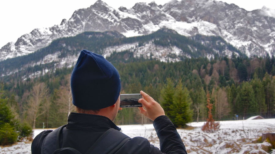 Rear view of person photographing in mountains
