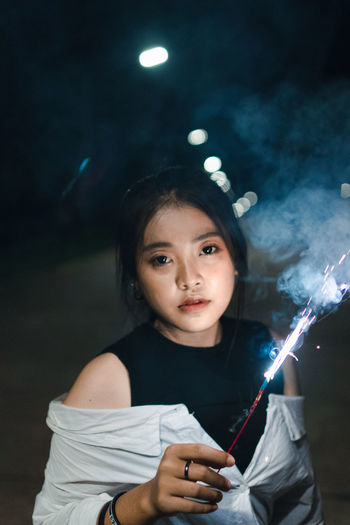 Portrait Of Young Woman Holding Illuminated Sparkler At Night