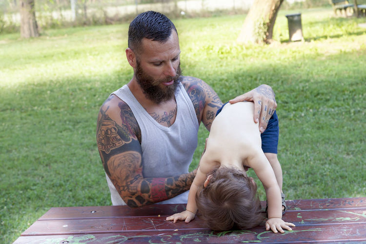 Bearded man playing with son on picnic table