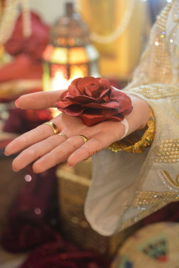 Cropped image of bride holding artificial rose