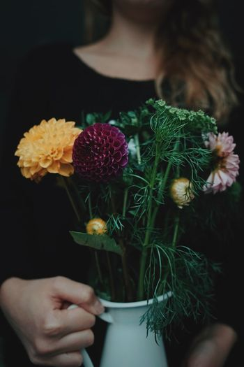 Midsection of woman holding flowers in vase