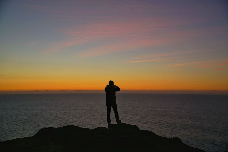 Silhouette man standing on rock at beach against orange sky