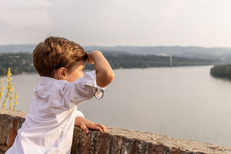 Rear view of boy looking at waterfall against sky