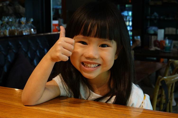 Portrait of smiling girl on table at restaurant