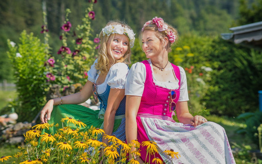 Smiling two friends sitting by flowering plants