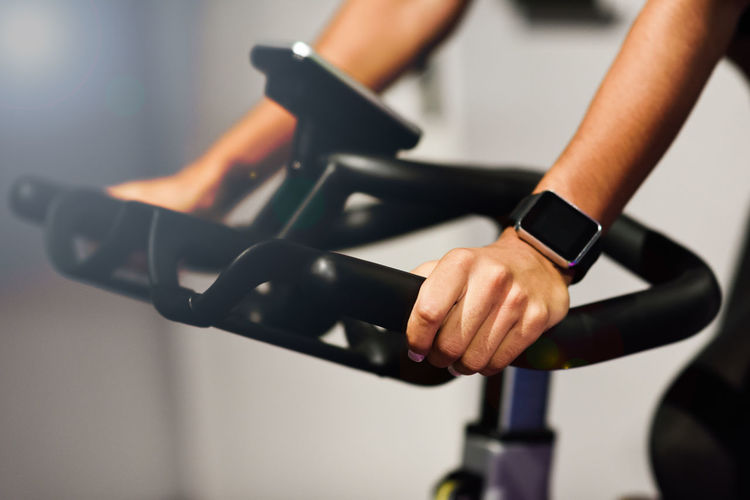 Hands of a woman training at a gym doing cyclo indoor with smart watch. Sports and fitness concept. Human Body Part Human Hand Indoors  Hand Midsection One Person Focus On Foreground Exercise Equipment Exercising Close-up Healthy Lifestyle Body Part Holding Sport Sports Training Lifestyles Standing Determination Adult Human Limb