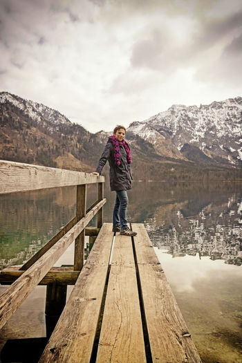 Woman standing on footbridge at lake against mountains
