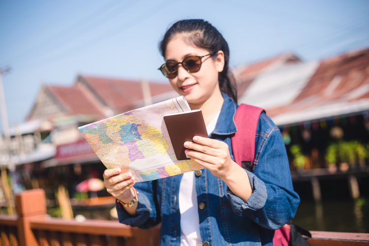 Smiling young woman reading map