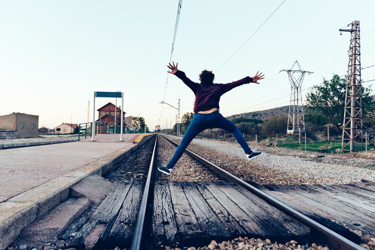Rear View Of Teenage Girl Jumping Over Railroad Tracks Against Clear Sky