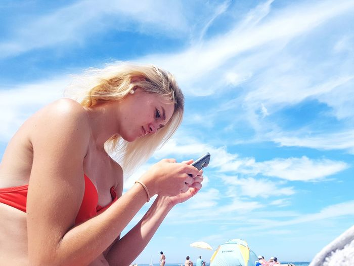 Side view of woman using mobile phone against sky