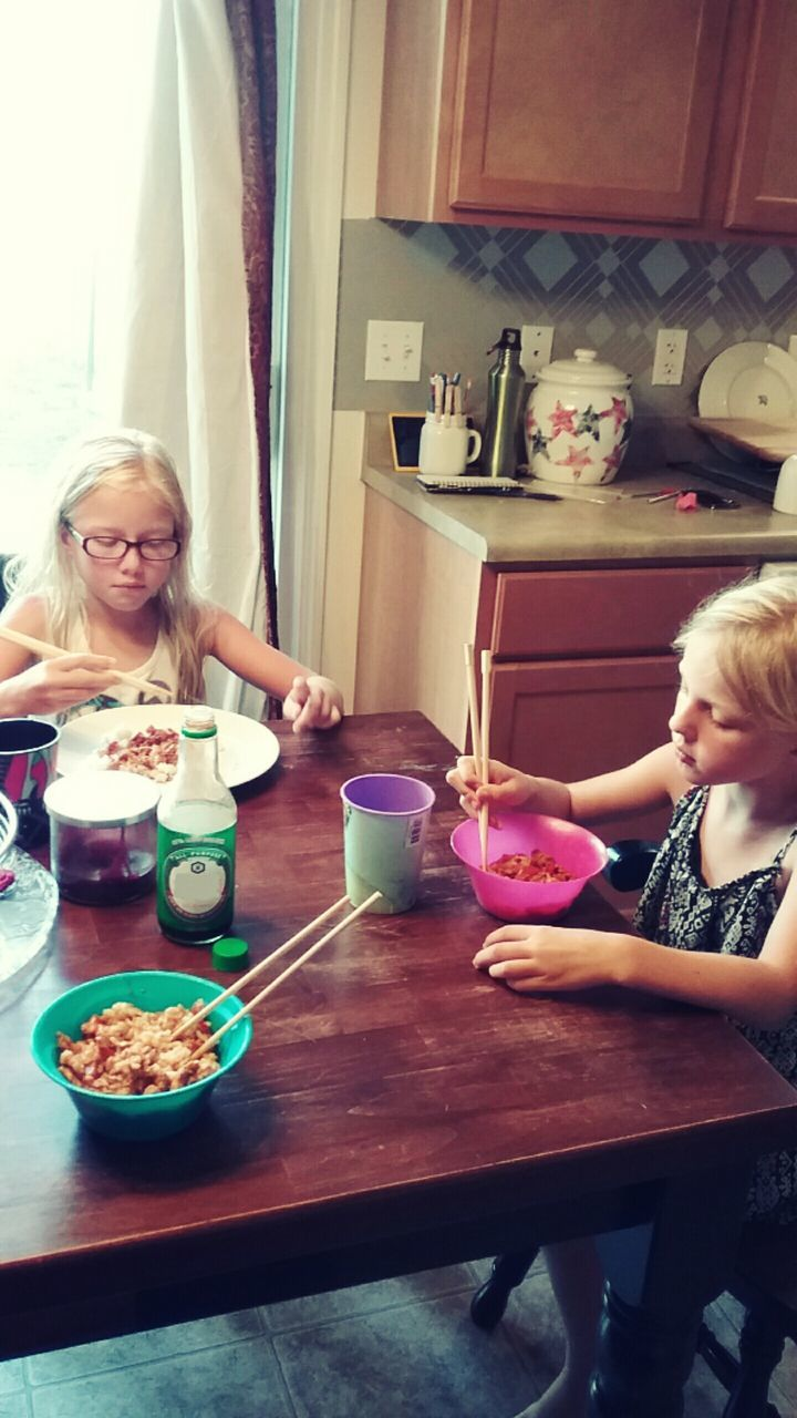 indoors, blond hair, togetherness, food and drink, real people, table, leisure activity, casual clothing, two people, childhood, sitting, home interior, lifestyles, young adult, young women, smiling, elementary age, happiness, bonding, food, front view, sibling, holding, drink, girls, friendship, freshness, wireless technology, day, people