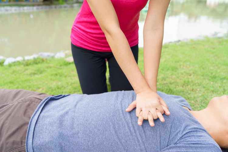 Midsection of woman giving cpr to man lying in grassy field