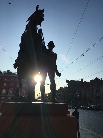 Statue on street in city against sky