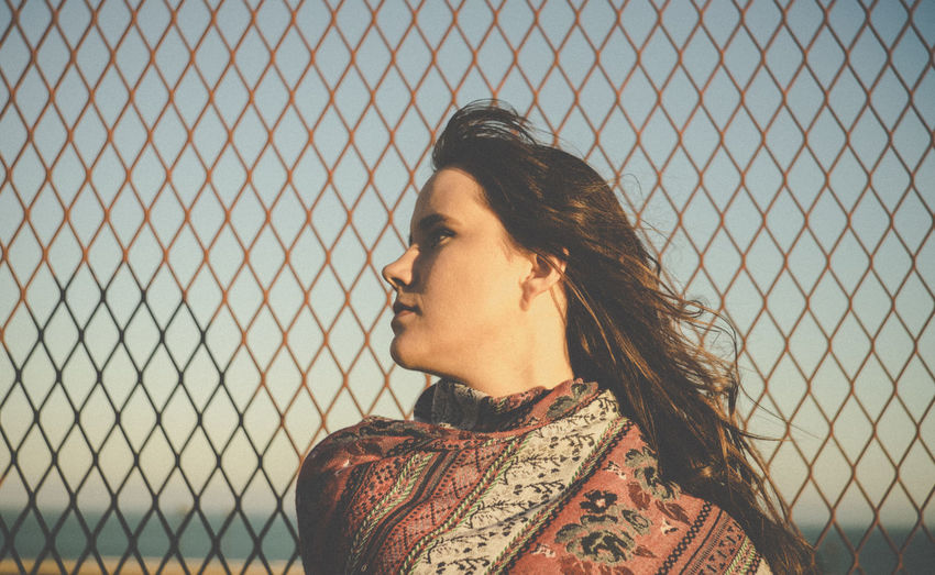 Young woman by chainlink fence