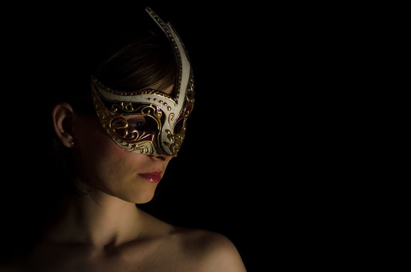 Topless woman wearing carnival mask against black background
