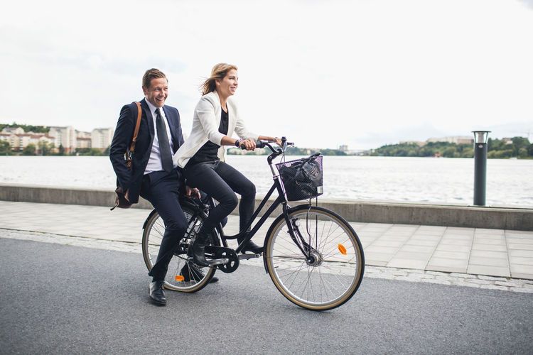 Man riding bicycle sitting on sidewalk in city