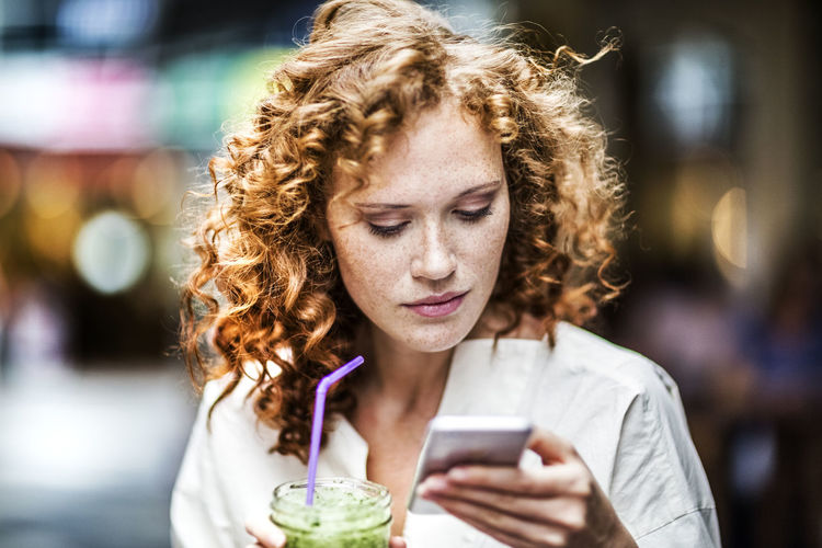 Portrait of woman holding mobile phone outdoors