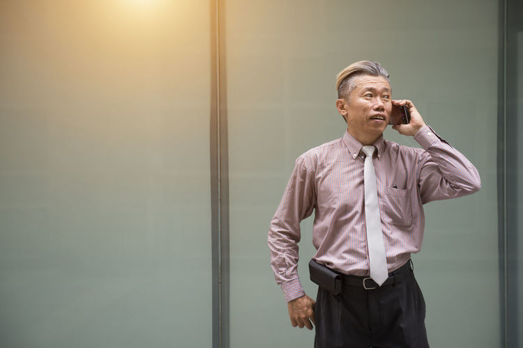 Well-Dressed Businessman Using Phone While Standing Against Building In City