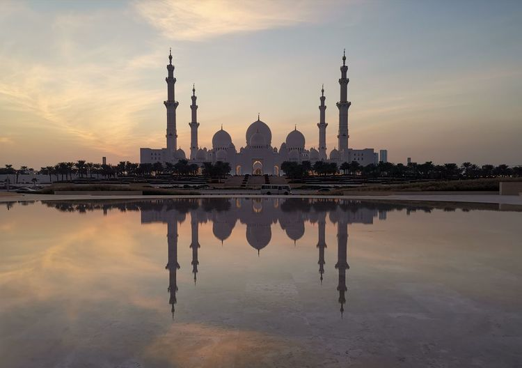 Reflection of mosque on lake in city during sunset