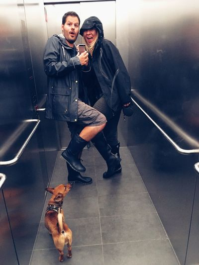 Portrait of young man and woman with dog on floor in elevator