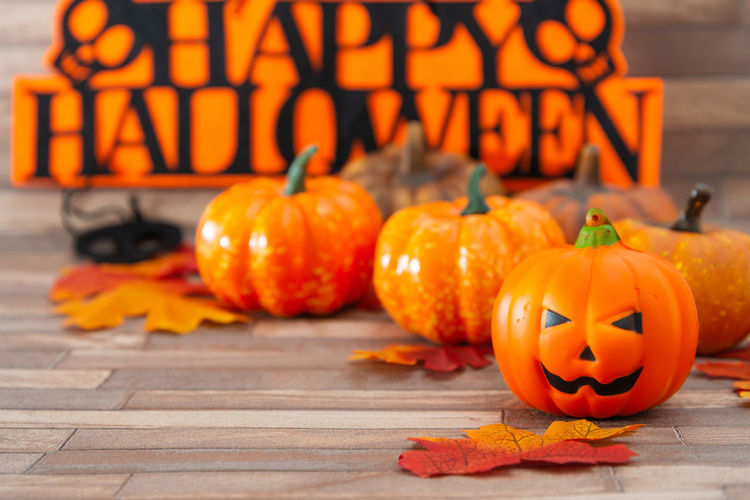 High angle view of pumpkins and text on wood during halloween