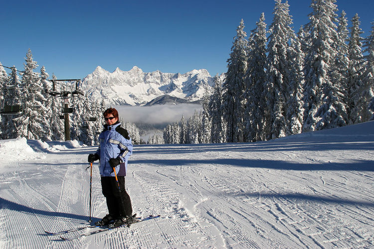 Full length of woman skiing on snow covered landscape during winter