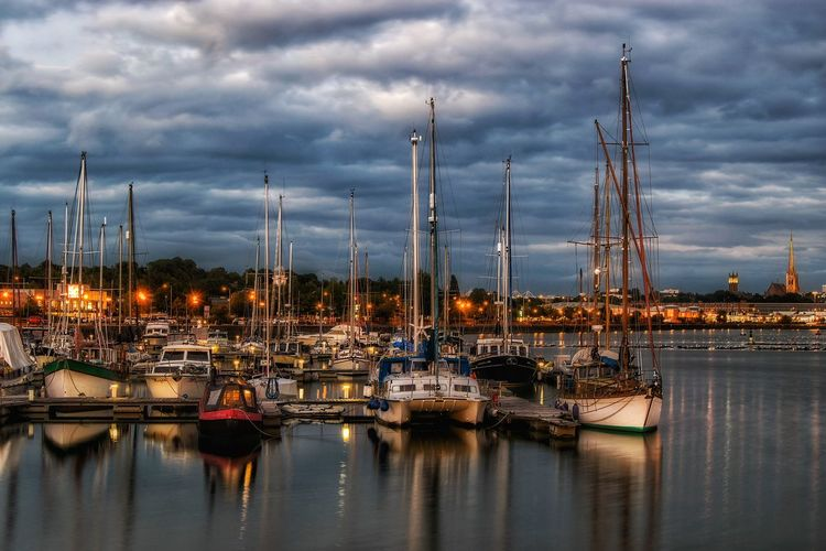 Boats moored at illuminated port during sunset against sky