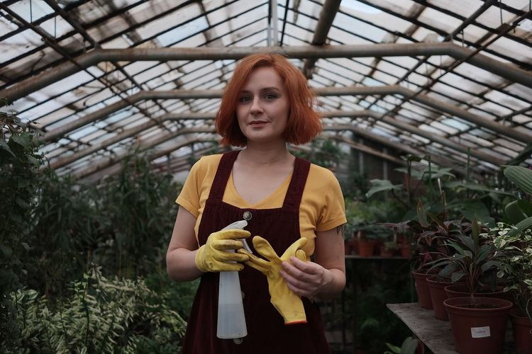 Portrait of beautiful young woman standing in greenhouse