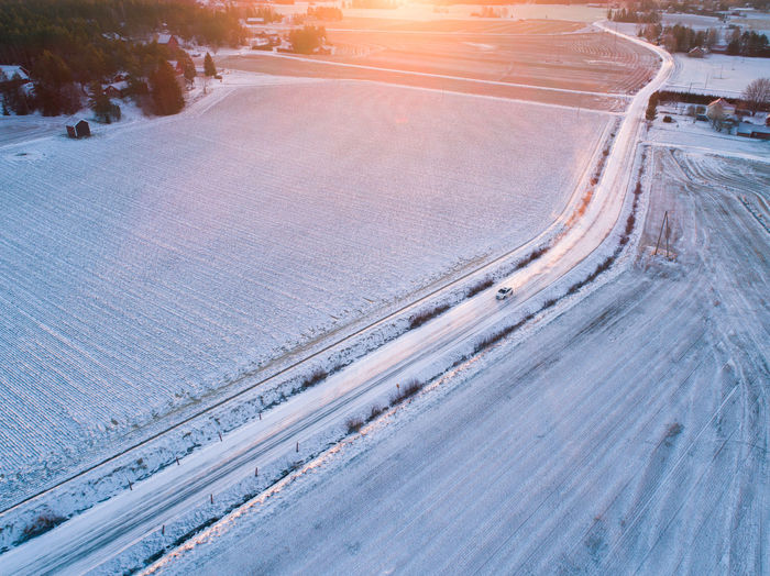 Aerial view of a car driving on country road at winter with golden sun leaking on background, Lieto, Finland DJI X Eyeem Aerial Dronephotography Aerialphotography Copy Space Aerial Shot Country Road Rural Aerial Photography Aerial View Beauty In Nature Car Cold Temperature Day Drone Photography Golden Hour Landscape Light Leak Nature No People Nordic Outdoors Road Scenics Snow Transportation Vehicle Winter High Angle View Shades Of Winter