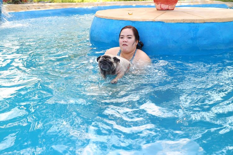 Woman with dog swimming in pool