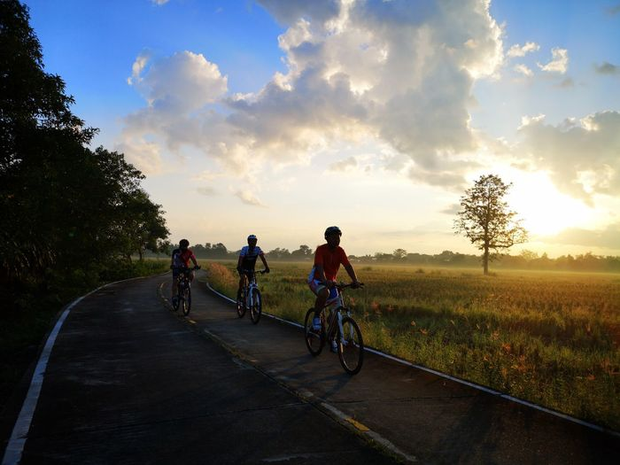 People riding bicycle on road against sky during sunset