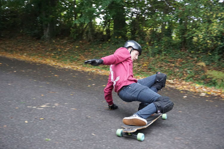 Longboarders in Southampton Common Skateboarding Adult Casual Clothing Clothing Day Forest Full Length Healthy Lifestyle Hood - Clothing Land Leisure Activity Lifestyles Motion Nature One Person Outdoors Plant Sport Sports Clothing Tree Women