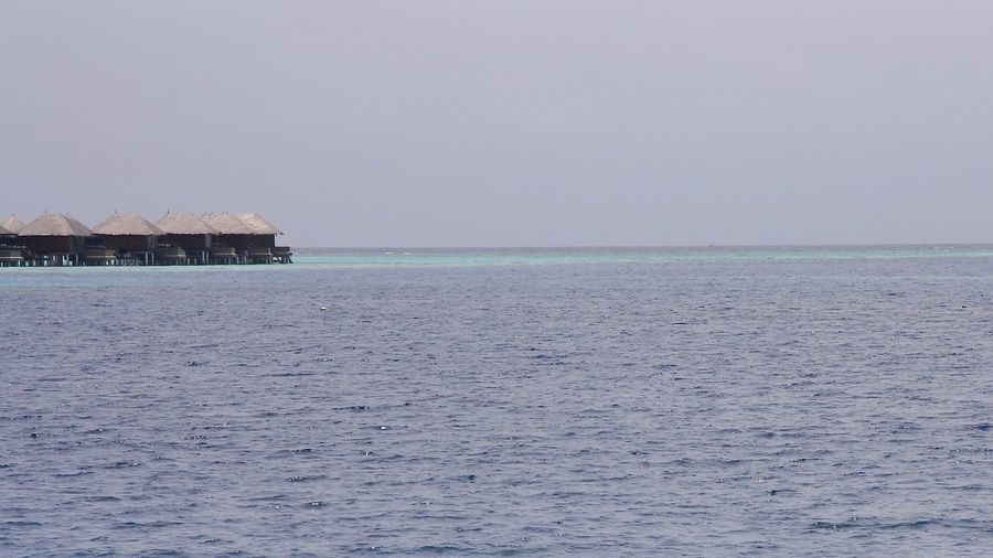 Seascape , Maldives Sea Tranquility Scenics Nature Beauty In Nature Tranquil Scene Thatched Roof No People Waterfront Architecture Water Clear Sky Built Structure Outdoors Horizon Over Water Building Exterior Sky Day Seascape Maldives Summer Seaview Travel Backgrounds Watervillage