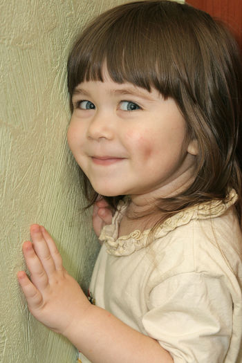 Portrait of cute girl against wall