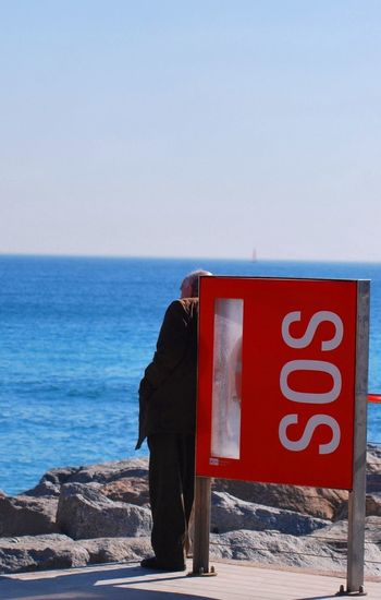 Close-Up Of Sos Sign Against Calm Blue Sea